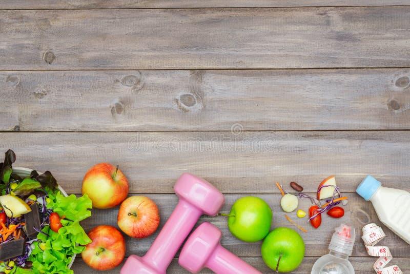 Vista superior do conceito saudável do estilo de vida, dos equipamentos de esporte e de alimentos frescos no fundo de madeira Vis foto de stock royalty free