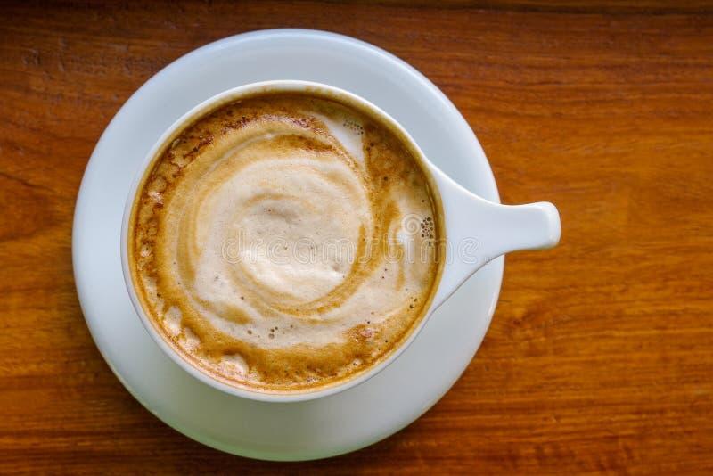 Vista superior do copo de café do cappuccino com espuma do leite no backgro de madeira imagem de stock