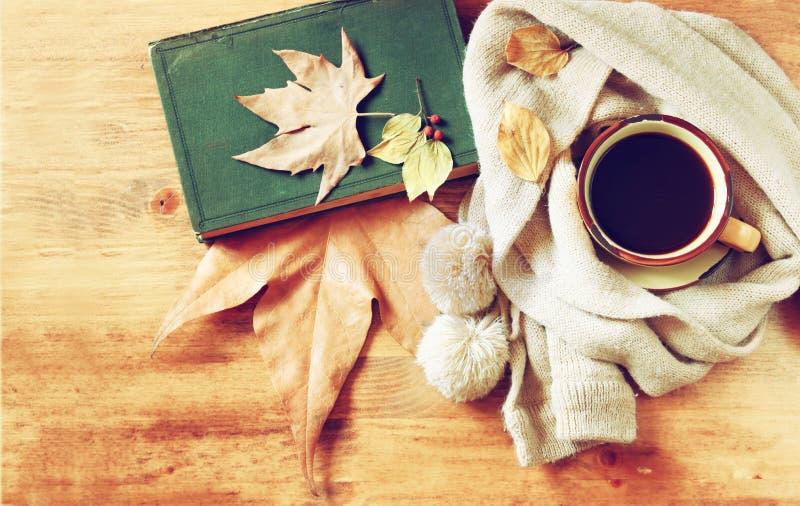 Vista superior do copo do café preto com folhas de outono, um lenço morno e o livro velho no fundo de madeira imagem filreted fotografia de stock royalty free