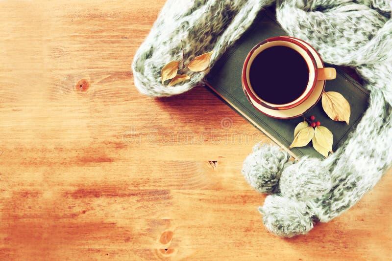 Vista superior do copo do café preto com folhas de outono, um lenço morno e o livro velho no fundo de madeira imagem filreted imagem de stock