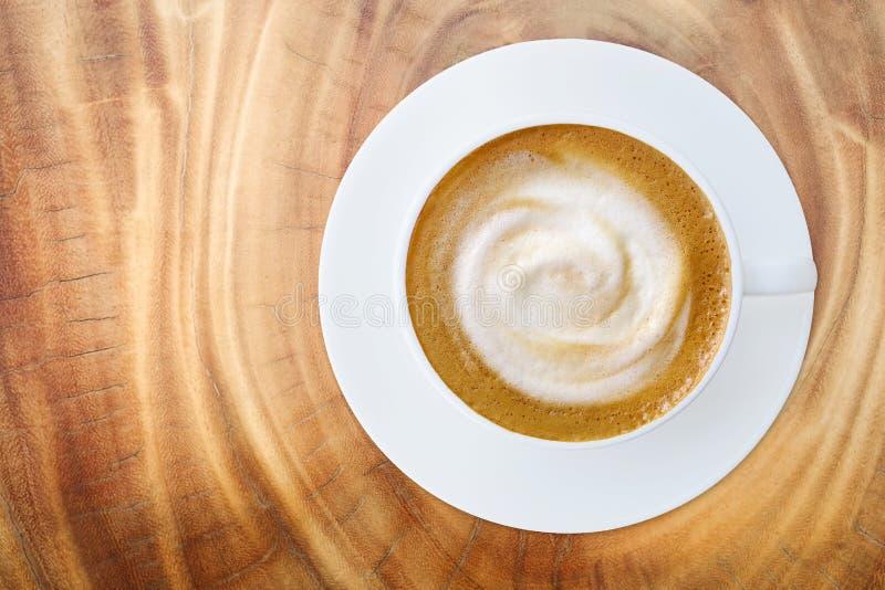 Vista superior do copo quente do latte do cappuccino do café com os pires na madeira fotografia de stock