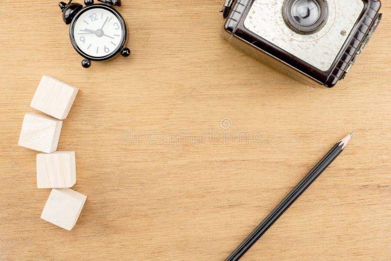 Vista superior do despertador, da câmera do vintage, do cubo de madeira e do lápis na tabela de madeira da mesa do grunge velho d foto de stock