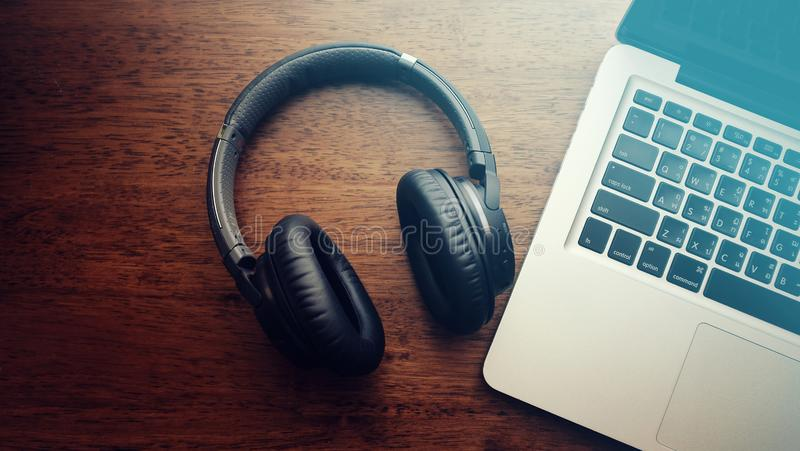 Vista superior do fones de ouvido preto do bluetooth com laptop imagem de stock