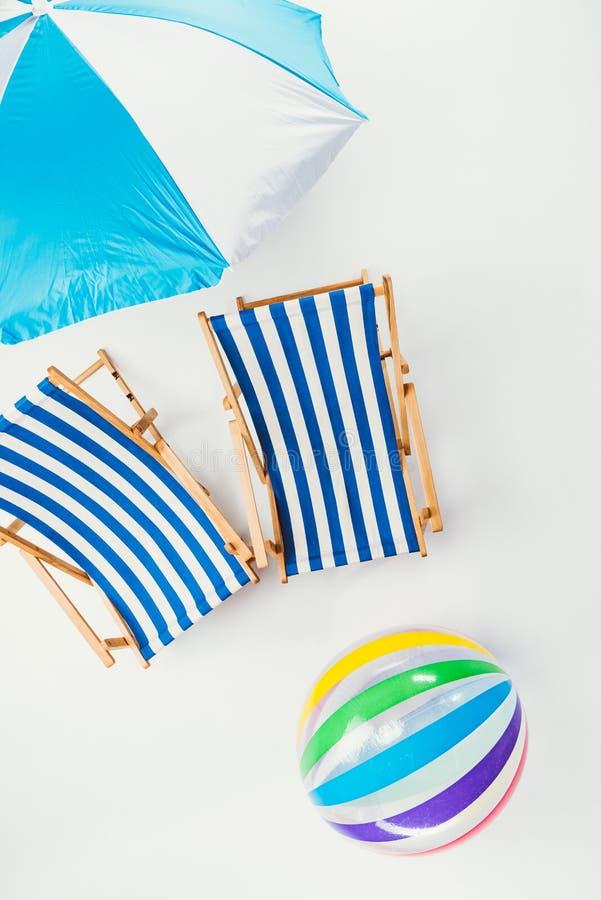 vista superior do guarda-chuva de praia, de cadeiras de praia listradas e da bola inflável fotografia de stock royalty free