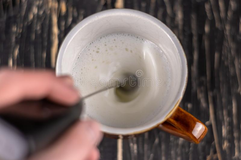 Vista superior do leite de vidro Vidro do leite de cima do fundo preto Leite de formação de espuma com mini-misturador foto de stock royalty free