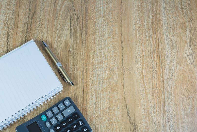 Vista superior do livro, da pena e da calculadora de nota na tabela de madeira imagem de stock