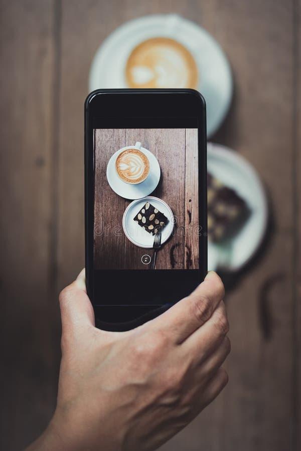 A vista superior do móbil da terra arrendada da mão toma uma foto do copo de café e do c imagem de stock royalty free