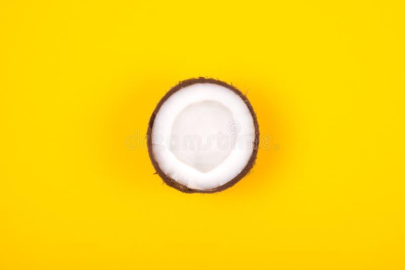 Vista superior do meio coco maduro no fundo amarelo brilhante Copie o espa?o fotografia de stock royalty free