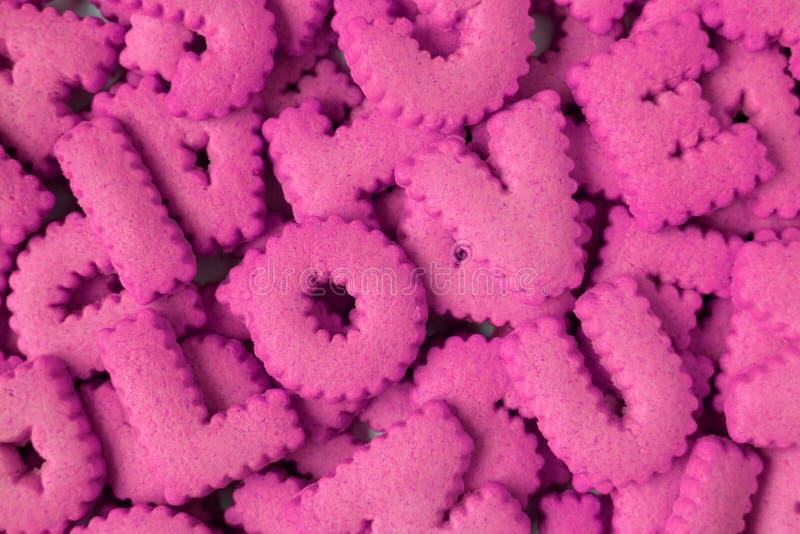 A vista superior do montão do alfabeto cor-de-rosa vívido deu forma aos biscoitos que soletram a palavra AMOR U imagens de stock