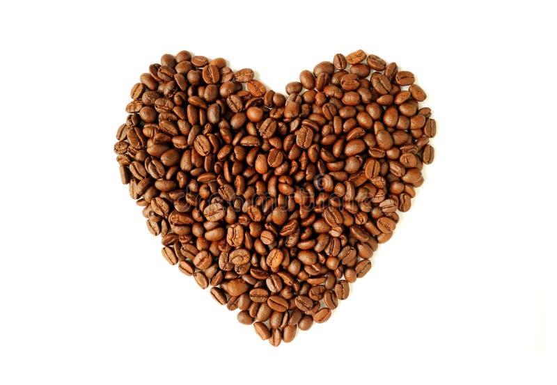 A vista superior do montão de feijões de café roasted no coração deu forma isolado no fundo branco imagem de stock royalty free