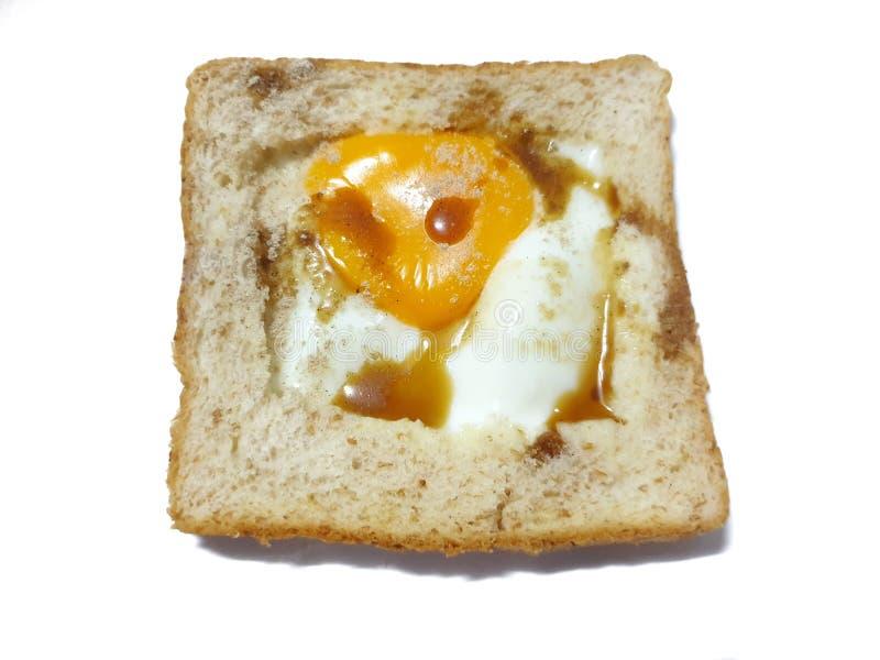 A vista superior do ovo frito em um pão integral inteiro do furo cobriu com molho e pimenta de soja fotografia de stock royalty free