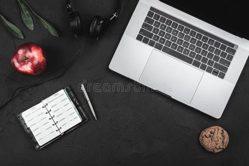 Vista superior do portátil e os fones de ouvido, o caderno e a pena, maçã vermelha em uma tabela preta fotografia de stock