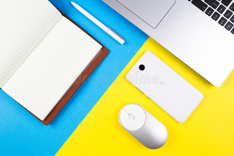 Vista superior do portátil, do rato do computador, do telefone celular, do caderno de papel aberto e da pena no fundo azul e amar fotos de stock