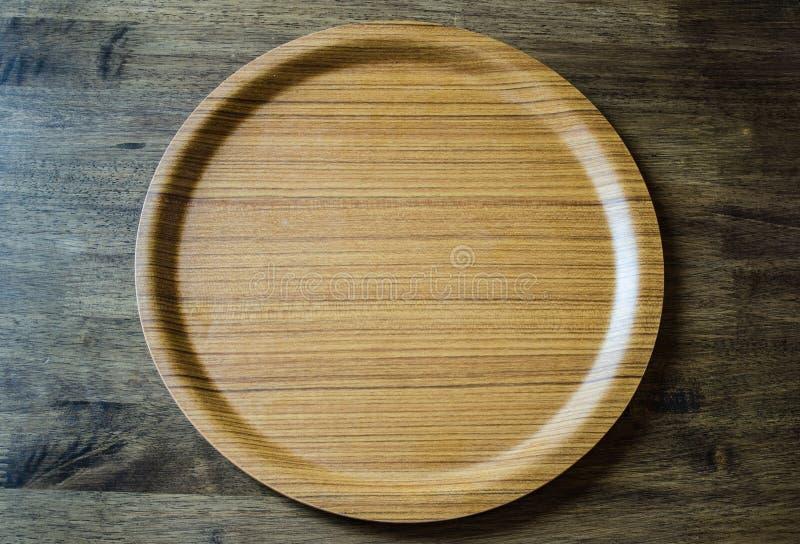 Vista superior do prato de madeira no fundo de madeira resistido imagem de stock