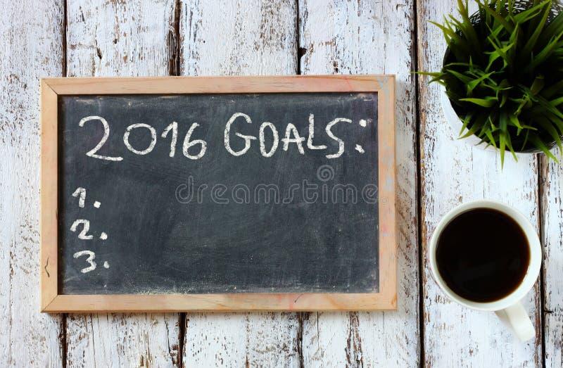 Vista superior do quadro-negro com os objetivos da frase 2016 sobre a placa de madeira com café fotos de stock royalty free
