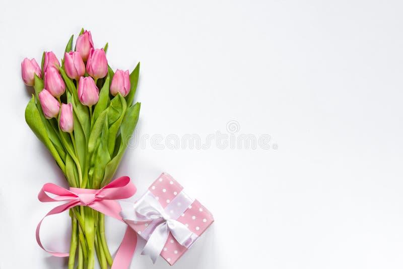 A vista superior do ramalhete cor-de-rosa das tulipas, envolvida com fita cor-de-rosa e rosa pontilhou a caixa de presente sobre  fotografia de stock royalty free
