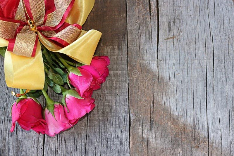Vista superior do ramalhete de rosas vermelhas com a fita no fundo velho da placa de madeira Espaço direito para a mensagem cartã fotos de stock royalty free