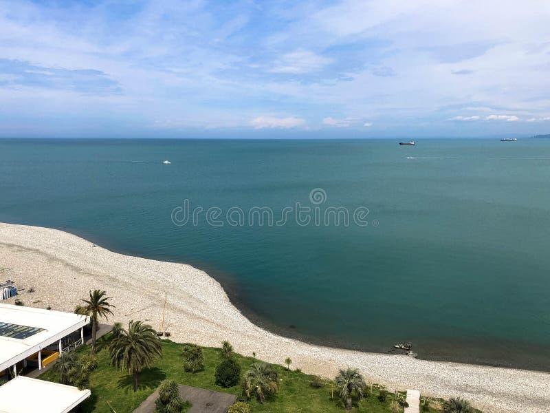 Vista superior do Sandy Beach com areia, do mar, das palmeiras verdes e das construções, casas em um recurso de verão morno tropi fotografia de stock royalty free