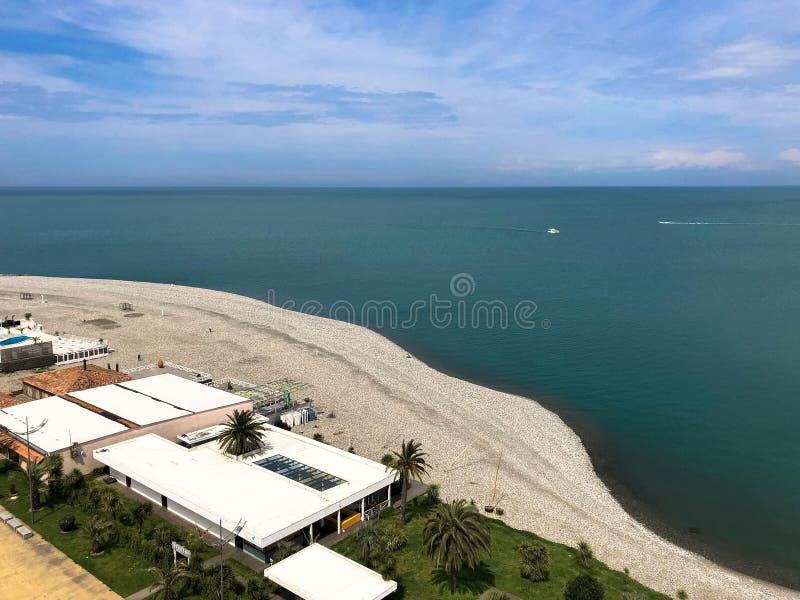 Vista superior do Sandy Beach com areia, do mar, das palmeiras verdes e das constru??es, casas em um recurso de ver?o morno tropi imagens de stock royalty free