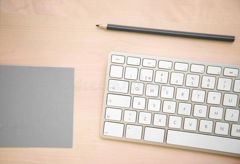 Vista superior do teclado de computador com lápis e papel de nota cinzento sobre foto de stock
