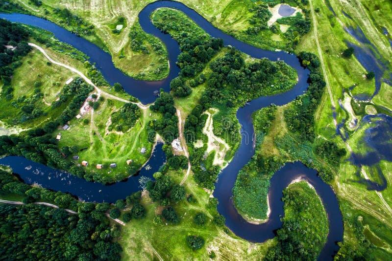 Vista superior do vale de um rio meandrando entre campos verdes fotografia de stock