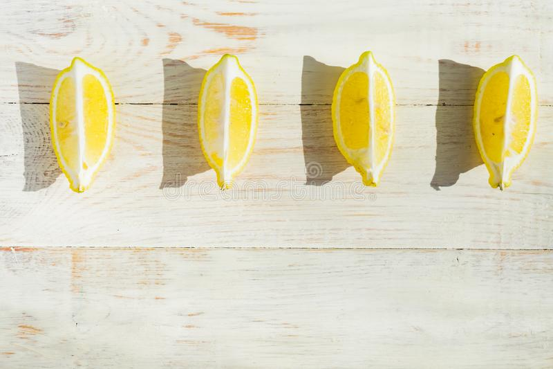 Vista superior dos limões de um quarto na tabela de madeira Sombras duras em um dia saunny foto de stock