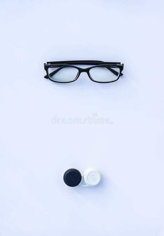 Vista superior dos monóculos e das lentes de contato no recipiente no fundo branco imagens de stock