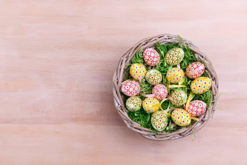Vista superior dos ovos da páscoa e das penas em uma cesta de vime em um fundo de madeira Cartão de cumprimentos de Easter fotos de stock royalty free