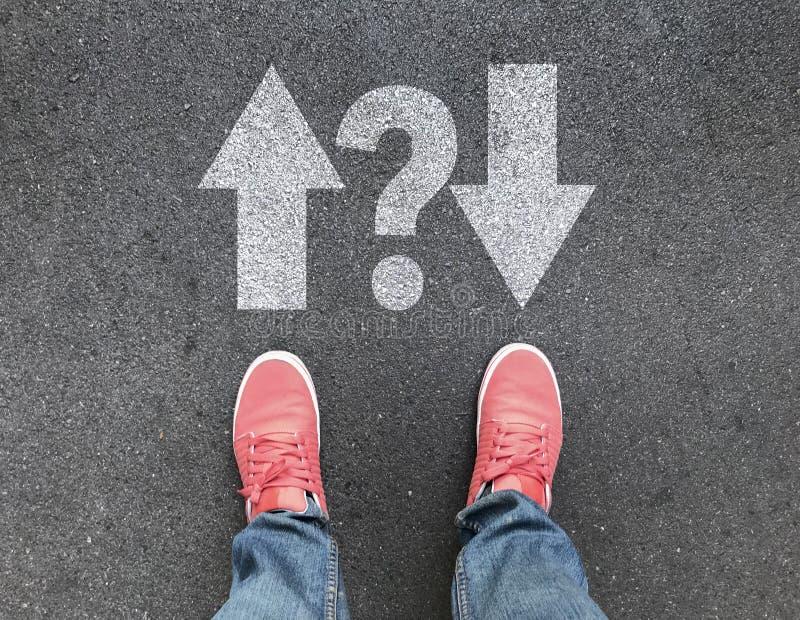 Vista superior dos pés e de setas diferentes do sentido com ponto de interrogação na estrada asfaltada fotos de stock