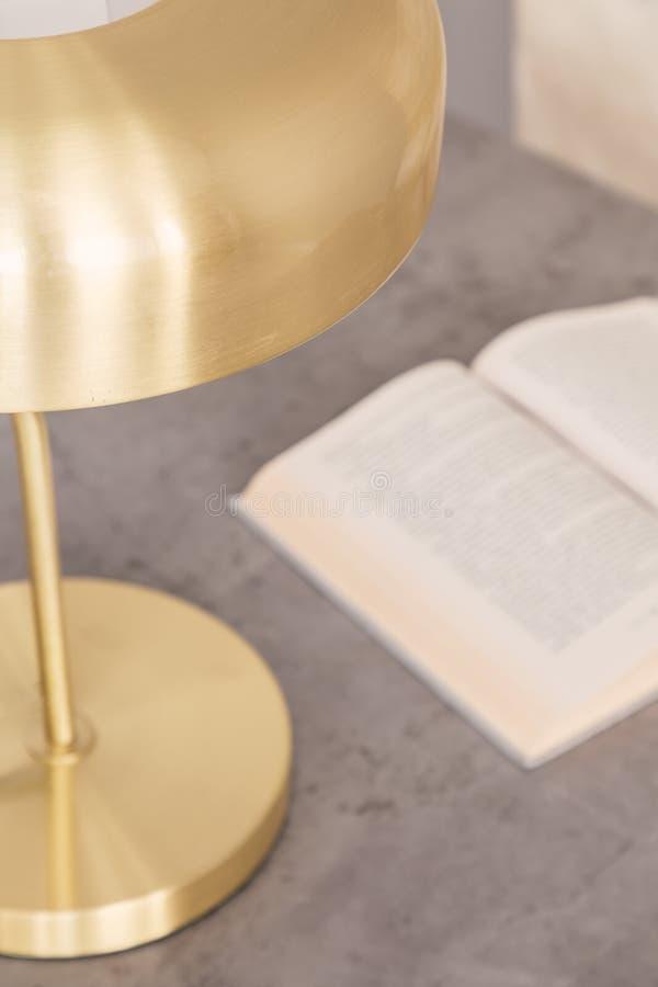A vista superior e o close-up de um ouro colorem a lâmpada que está ao lado de um livro aberto em uma parte superior de mármore c fotos de stock royalty free