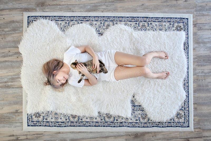 Vista superior E O gato no abra?o da mulher que encontra-se no tapete de l?s imagens de stock royalty free