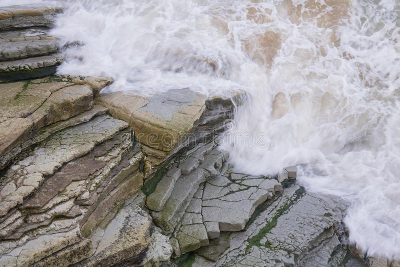 Vista superior em superfície movente da água do mar com ondas e espuma contra rochas, teste padrão do fundo da textura fotografia de stock