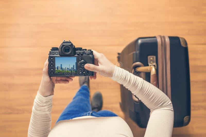 Vista superior em uma menina que olha uma cidade de Chicago das fotos em sua posição da câmera com a mala de viagem no aeroporto  fotos de stock