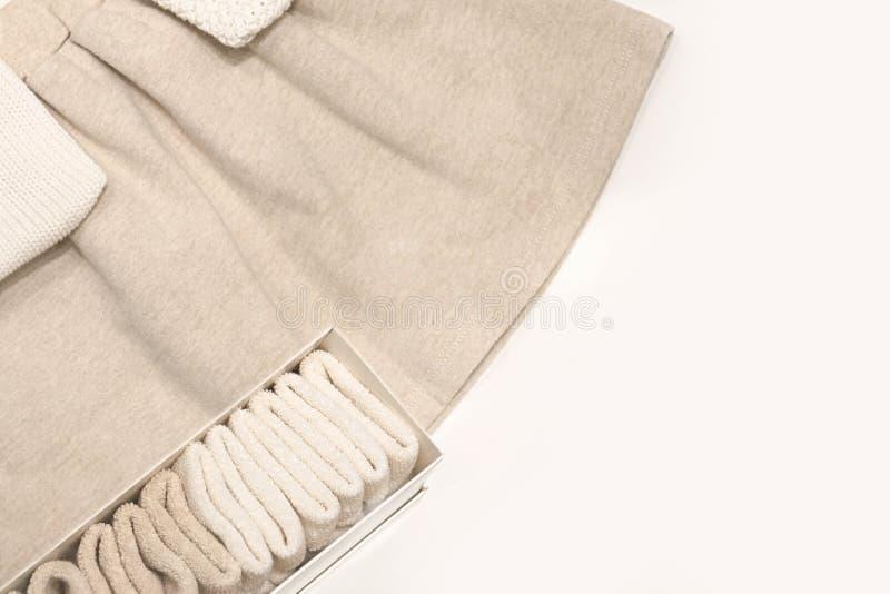 Vista superior em uma saia bege, nas camisetas e nas peúgas feitas das telas naturais que se encontram na tabela imagens de stock