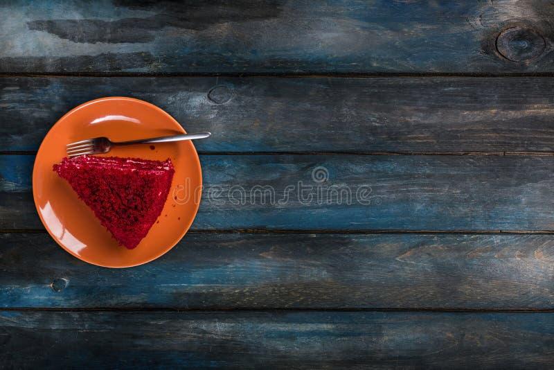 Vista superior Fatia de bolo vermelho delicioso de veludo em uma placa cerâmica com uma forquilha em um fundo de madeira colorido imagens de stock