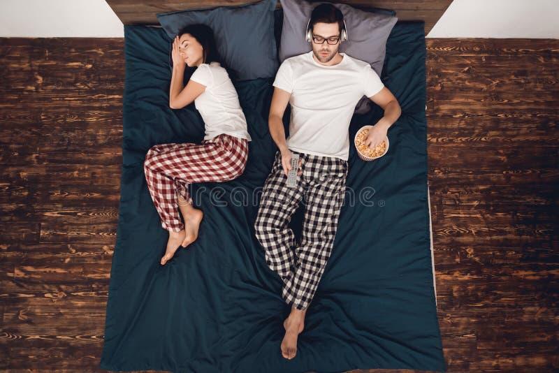 Vista superior Filme de observação do homem novo e pipoca comer na cama quando a mulher dormir próximo imagens de stock royalty free