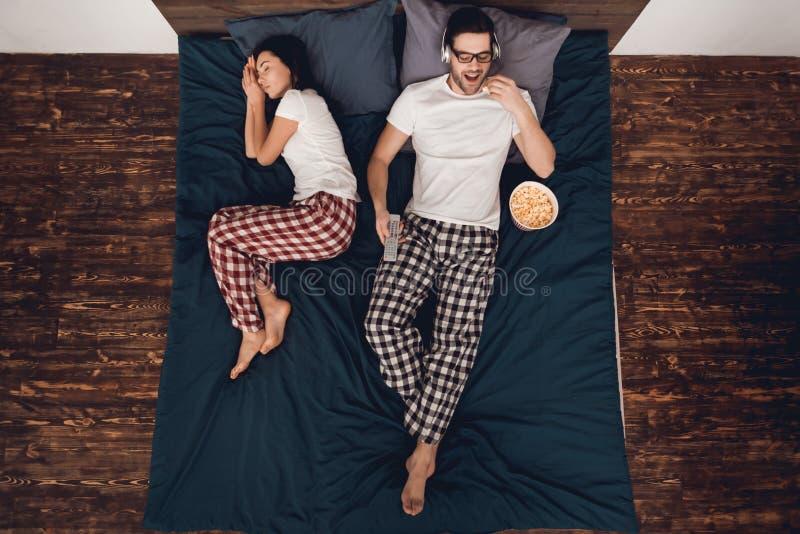Vista superior Filme de observação do homem novo e pipoca comer na cama quando a mulher dormir próximo foto de stock royalty free