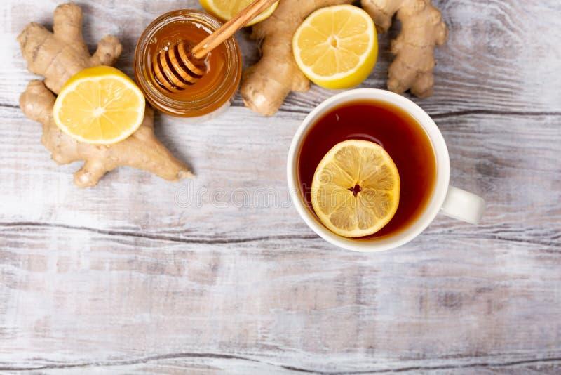 Vista superior Fim acima Conceito saudável Chá, limão, gengibre, mel em um fundo de madeira branco Configuração lisa Tratamento d foto de stock