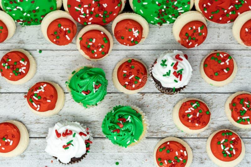 Vista superior flatlay de deleites do feriado do Natal - os queques e as cookies de açúcar do buttercream com polvilham foto de stock
