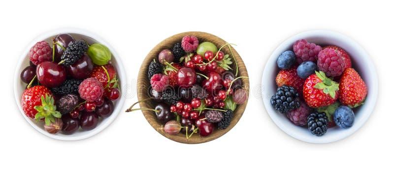Vista superior Frutos e bagas na bacia isolada no fundo branco Framboesas, cerejas, morangos, amoras-pretas e azul maduros fotografia de stock