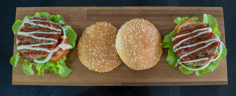 Vista superior, ingredientes dos Hamburger colocados em uma placa de corte de madeira imagem de stock