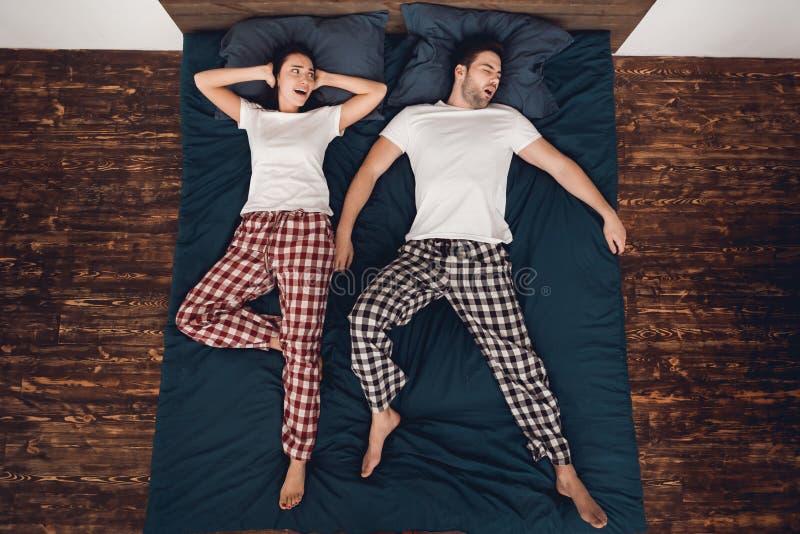 Vista superior A jovem mulher alarmada fecha as orelhas devido ruidosamente a ressonar do homem adulto que dorme próximo fotos de stock