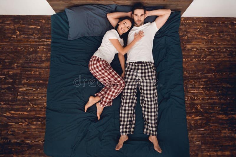 Vista superior A jovem mulher bonita encontra-se perto do homem com os braços dobrados na parte traseira de cabeça imagem de stock