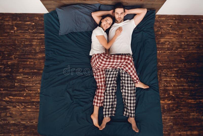 Vista superior A jovem mulher bonita está encontrando-se ao lado do homem considerável Poses do sono para pares fotos de stock