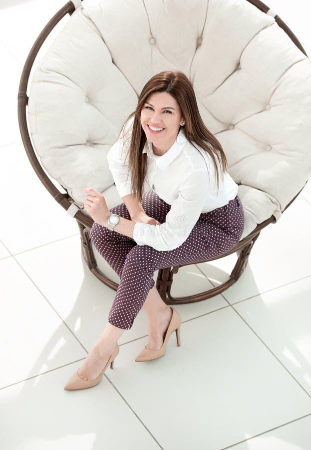 Vista superior jovem mulher que senta-se na cadeira redonda macia fotografia de stock