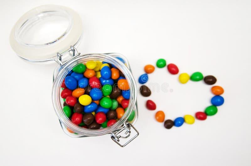 Vista superior, lotes de doces coloridos no frasco transparente no fundo branco imagem de stock