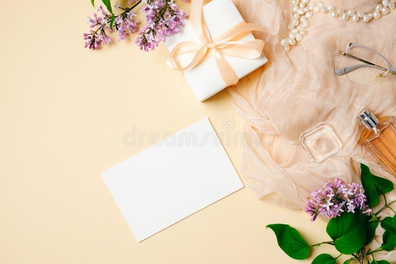 Vista superior, a mesa das mulheres lisas da configuração Lenço lilás do flor, o de seda, vidros, garrafa de perfume, caixa de pr foto de stock