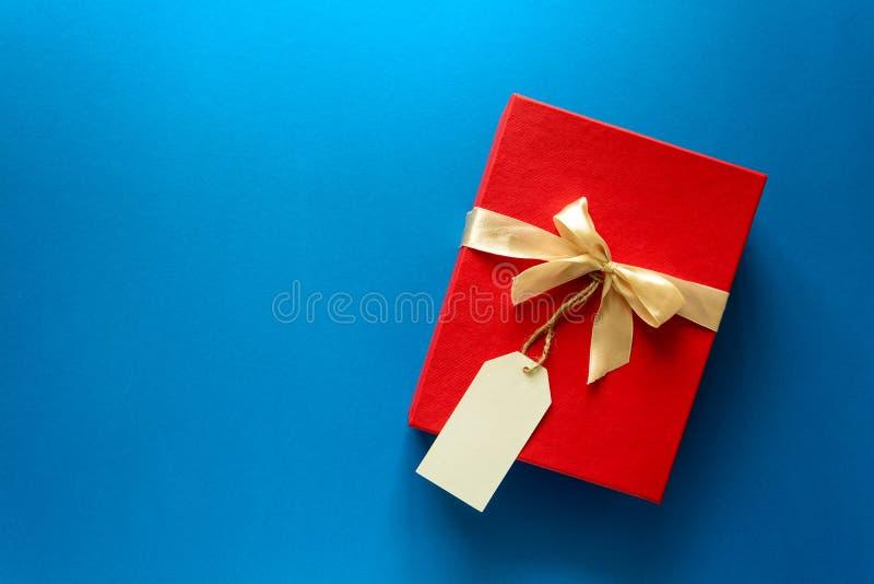 Vista superior na caixa de presente vermelha do Natal decorada com a fita no fundo do papel azul fotos de stock royalty free