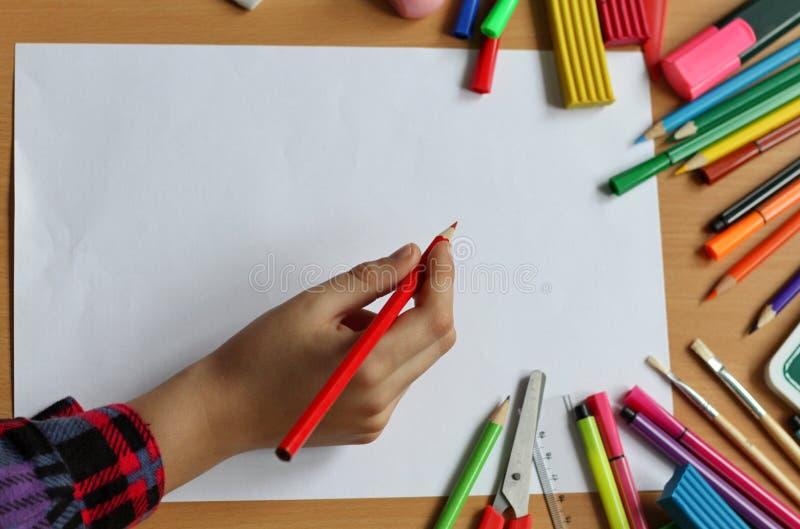 Vista superior na tabela com a folha de papel vazia e a mão do bebê com lápis De volta à escola A cor pinta com escovas de pintur imagens de stock royalty free