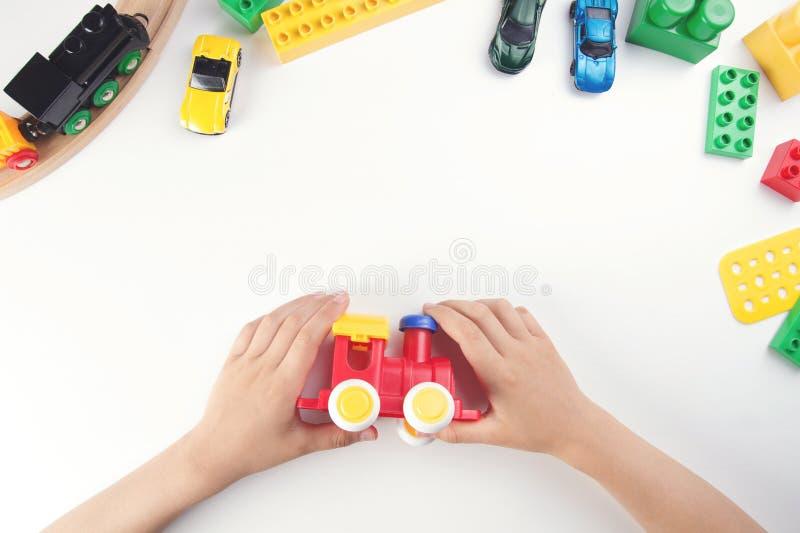 Vista superior nas mãos do ` s da criança que jogam com trem do brinquedo e muitos brinquedos no fundo branco da tabela foto de stock royalty free